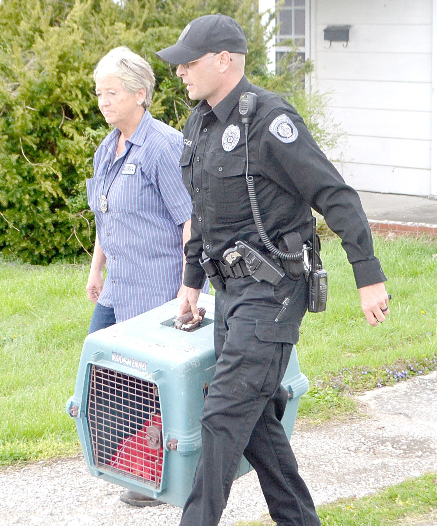 Officers carry the remains of the deceased dog from the residence of Howard Tinnell. Courtesy Anderson News