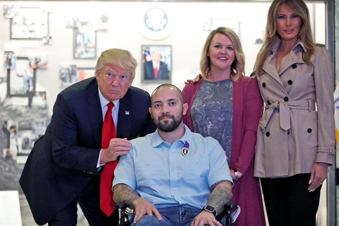 (AP Photo/Alex Brandon) President Donald Trump stands with U.S. Army Sgt. 1st Class Alvaro Barrientos, after awarding him with a Purple Heart, as first lady Melania Trump, right, stands with Tammy Barrientos second from right, at Walter Reed National...