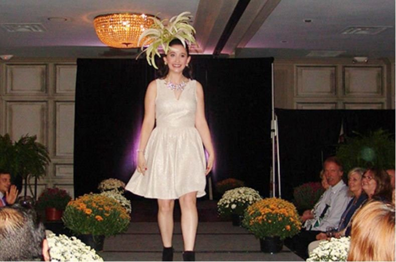 A girl in a gold dress walks down a runway