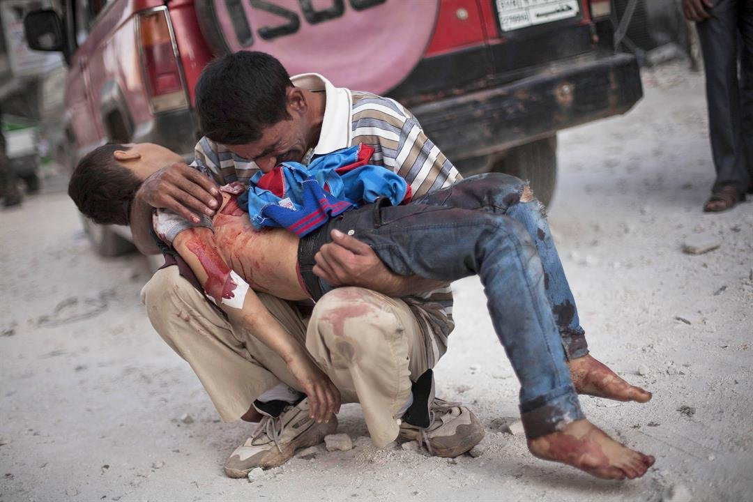 In this Wednesday, Oct. 3, 2013 file photo, a Syrian man cries as he holds the lifeless body of his son, killed by the Syrian Army, near Dar El Shifa hospital in Aleppo, Syria.(AP Photo/Manu Brabo, File)